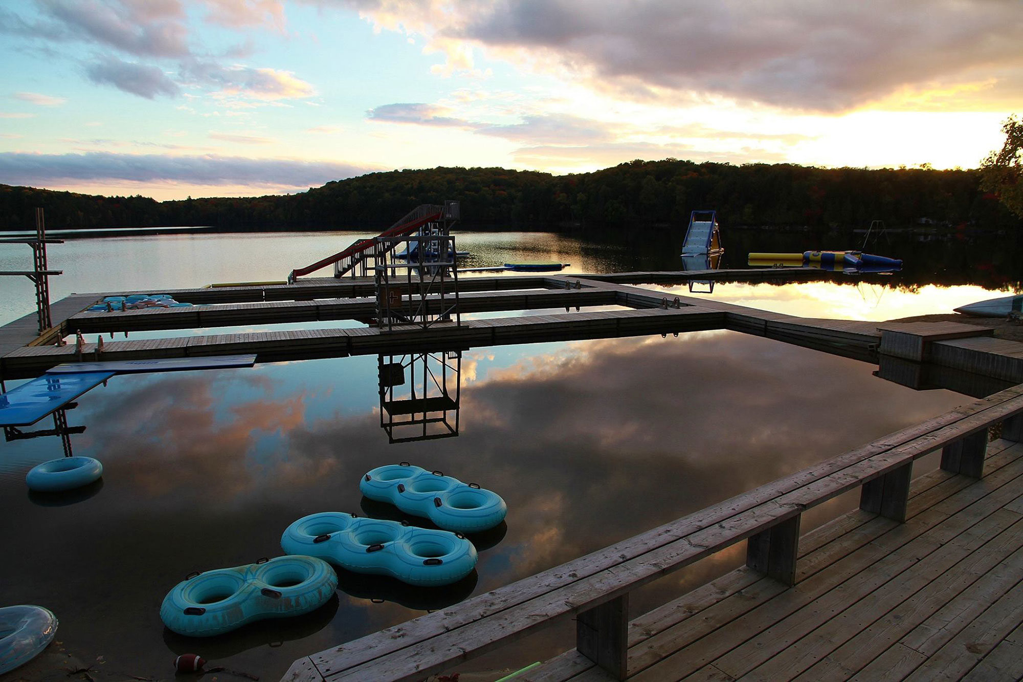 Camp Timberlane Dock at sunset with inner tubes and water slides in the water