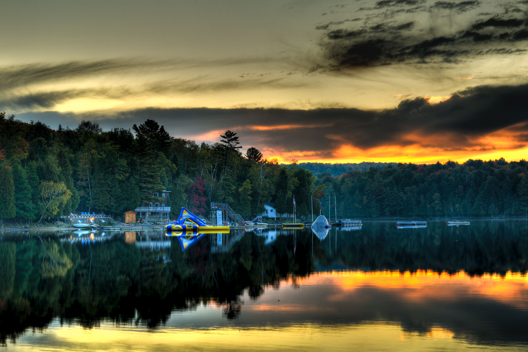 Camp Timberlane Lake at sunset with water activities and tree line in background